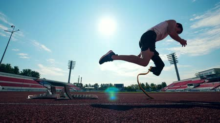 physically : Athlete with a leg substitute starts running Stock Footage