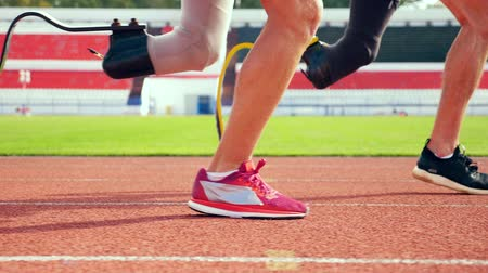 overcoming : Close up of healthy and prosthetic legs while running