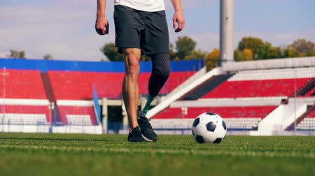 desvantagem : A man with a leg substitute is putting it onto the ball