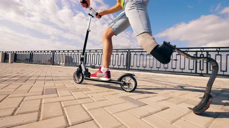 amputated : A man with a leg substitute is riding a scooter Stock Footage