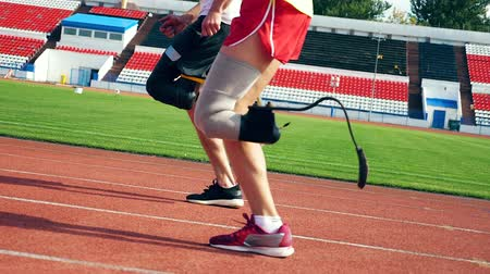 physically : Close up of artificial and healthy legs of athletes while running Stock Footage