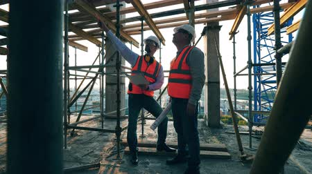 andaime : Male engineers are planning constructions among the scaffolding