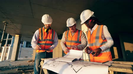 unfinished : Group of engineers in safety wear are discussing layouts on a construction site. Stock Footage