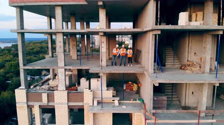 незаконченный : Team of engineers standing in the multistory project site