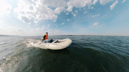 lancha : Zoom-out of an inflatable boat with a man in it