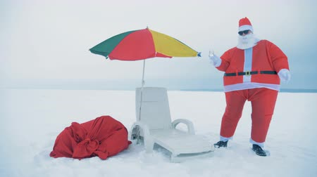 snowbound : Dances of Santa Claus with champagne in his hand next to a deck-chair Stock Footage