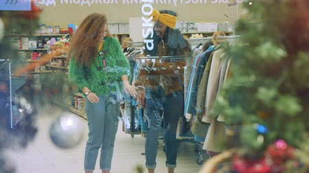 new clothes : Women try on jackets in a store before holidays.