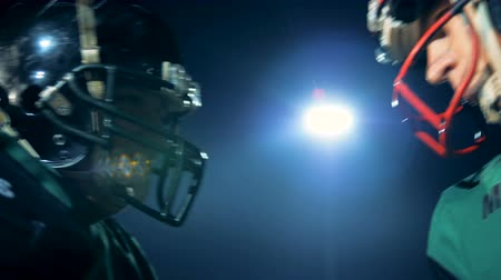 american football player : American football players bumps their heads in helmets, side view.