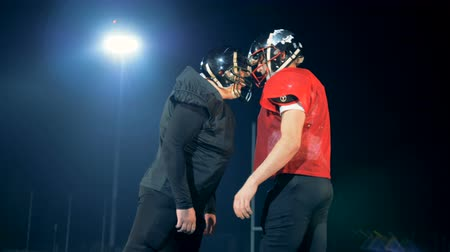 шлем : American football players bump their heads on a football field, side view. Стоковые видеозаписи