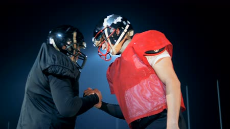american football player : American football opponents bump their heads, greeting each other, side view.