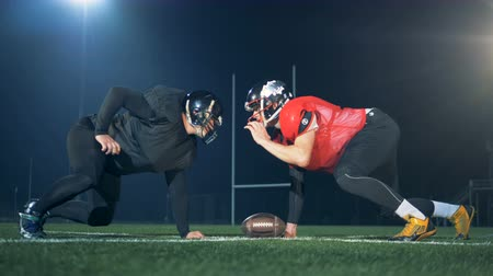 соперничество : American football players competing on a football field, side view.