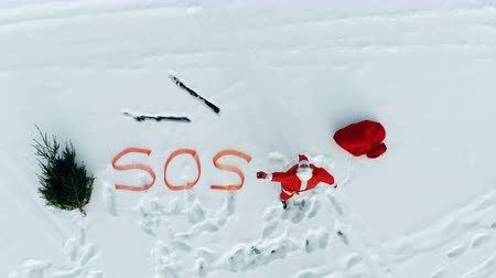 sos : Santa Claus is calling for help while standing in the snow