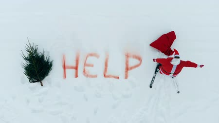 crashed : The word help is written in the snow near crying Santa Claus