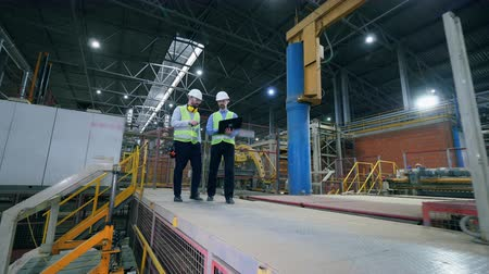 brick factory : Men walk in a factory facility, working with a laptop. Factory male engineers in a modern factory. Stock Footage