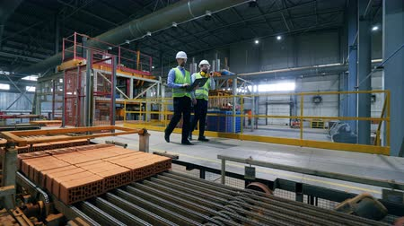 погрузчик : Male engineers walk at a modern industrial plant, checking pallets with bricks.