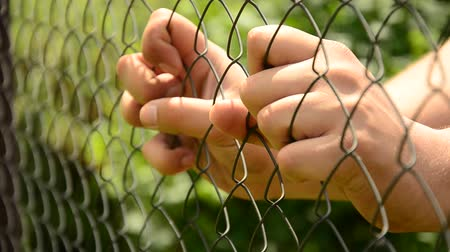 płot : Hands compressed metal fence. Help the person. Break loose