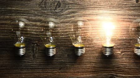 innováció : glowing bulb on the brown wooden background. Many lamps and lights up only one. concept ideas