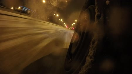 all ages : Wheel closeup on snowy roads. The car rides on a snow-covered streets of the city