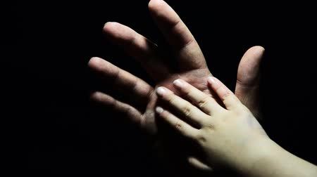 kezek : hand of an adult and child in the dark. A helping hand in a difficult moment