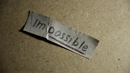 szavak : impossible turns to possible. Changing the word impossible to possible. Man makes the impossible possible Stock mozgókép