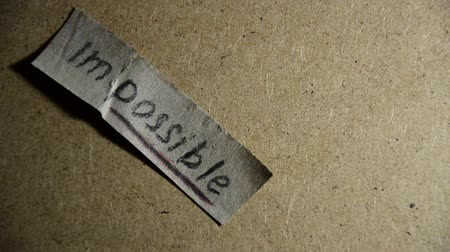 feasible : Word impossible fall to the floor. Changing the word impossible to possible. Man makes the impossible possible
