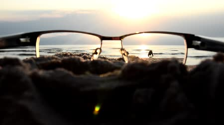 látomás : Optical glasses on the beach. To see well through the glasses. The concept of good vision Stock mozgókép