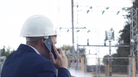 zangado : angry engineer screaming, talking on the phone against a power plant background Stock Footage