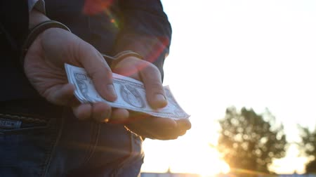 voltů : A man in a jacket holds money dollars in handcuffs, close-up, sunset, arrest, handcuffs