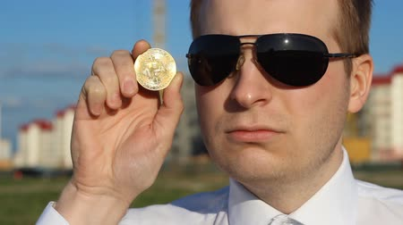 rejoice : A man in black glasses is holding a bitcoin in his hand and is sad, sad, curly plan Stock Footage