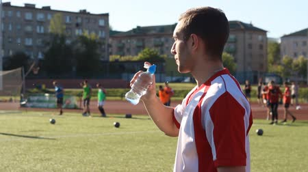 esportivo : Tired player is drinking a water during the training Stock Footage