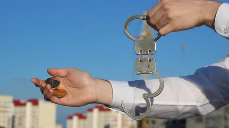 kajdanki : A man holds a bitcoin and etherium in his hand, handcuffs in the other hand, corruption, bribe