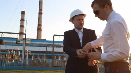 kajdanki : The policeman handcuffs the boss, delays, against the backdrop of the power plant, sunset, bribe, arrest Wideo