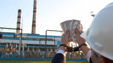 kajdanki : A man in handcuffs counts money dollars against a power plant background, sunset, close-up