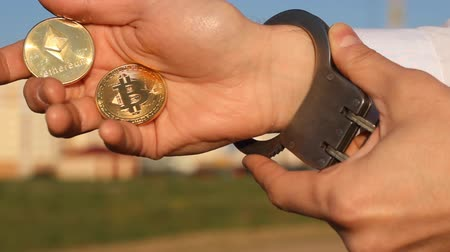 kajdanki : A man holds in his hand bitcoin and etherium, handcuffs, hand, close-up, handcuffs
