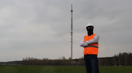 gsm : A man in a black mask and an alarm jacket is standing near the radio tower, a spy