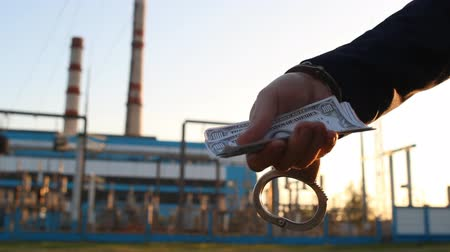 kajdanki : a mans hand in a jacket holds money dollars in handcuffs against a power plant background, sunset, close-up