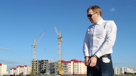 łapówka : The chief inspector in black glasses stands in handcuffs with money dollars against the background of construction Wideo