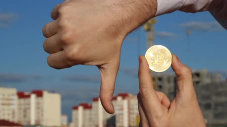 rejoice : male hands holding bitcoin and thumb down, falling, waning, close-up, bitcoin, thumb down Stock Footage