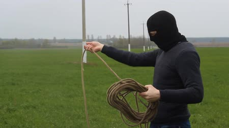 A man in a black mask with a rope tries to steal high-voltage wires