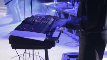 skladatel : A man on stage is playing a synthesizer, a concert