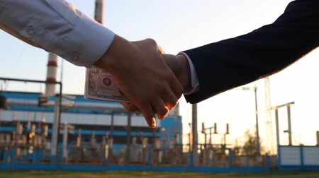 zloděj : A hand with money dollars against a power plant background is handcuffed, close-up, sunset, bribe, arrest