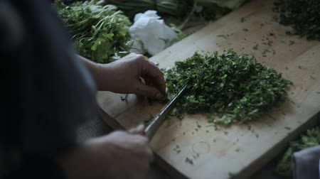Woman slices greens on a chalkboard, close-up
