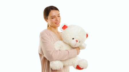 Young woman is hugging a white teddy bear with red pieces, isolated 動画素材