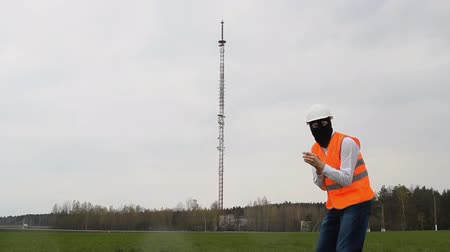 vysílač : A man in a black mask rubs his hands against the back of the telephone tower