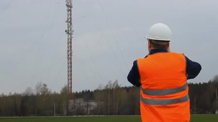 Inspector worker photographs a telephone tower on a camera