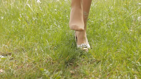 A girl in nature takes off her shoes, close-up, grass