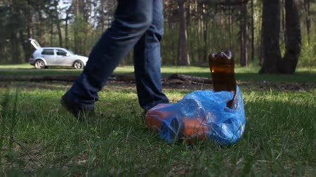 A man throws rubbish in the woods, close-up, trash Stok Video