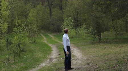 A man walks through the forest and drinks water from a bottle, a forest road, nature