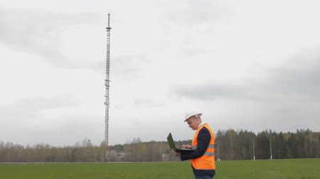 A man inspector prints in a laptop and checks a television tower