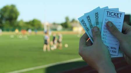 The man holds a winnings from the bookmaker office, in the hands of the euro money in the background of the stadium where players play football, close-ups, sports betting Stok Video